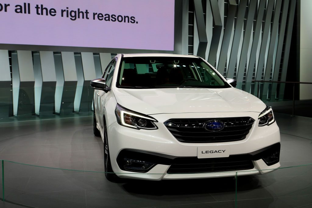 A white Subaru Legacy on display at an auto show