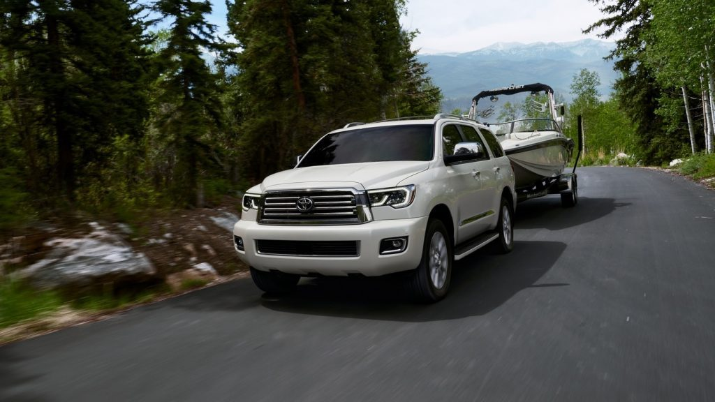 a white Toyota Sequoia pulling a boated on a forest-lined road
