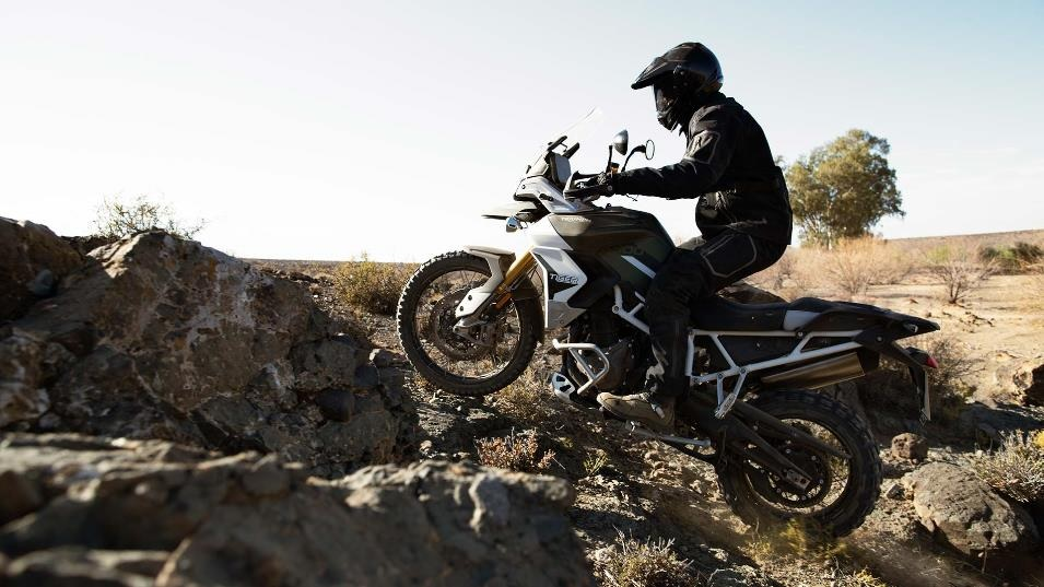 White-and-black 2020 Triumph Tiger 900 Rally Pro scrambling over rocks in the desert