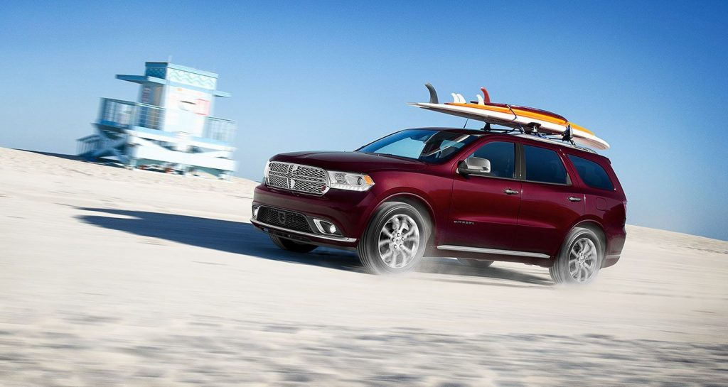 A red Dodge Durango toting surf boards on the beach
