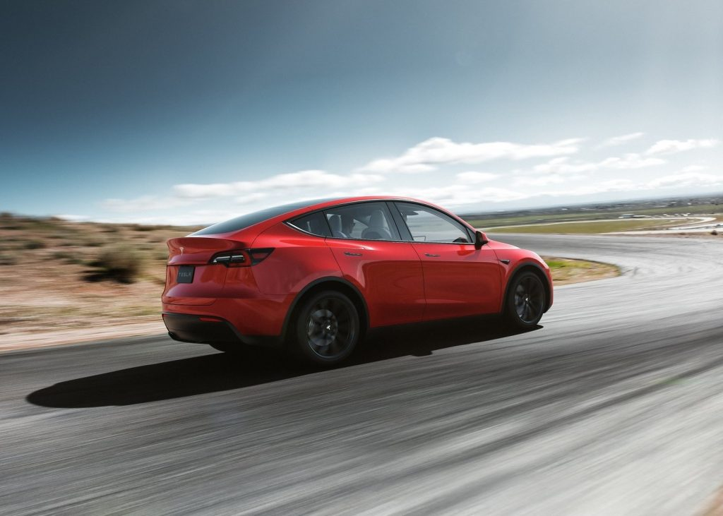 Red 2021 Tesla Model Y rear view, while it drives on a curvy road