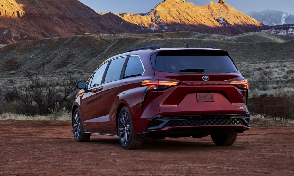 a deep red all-new Toyota Sienna, rear view in a desert landscape