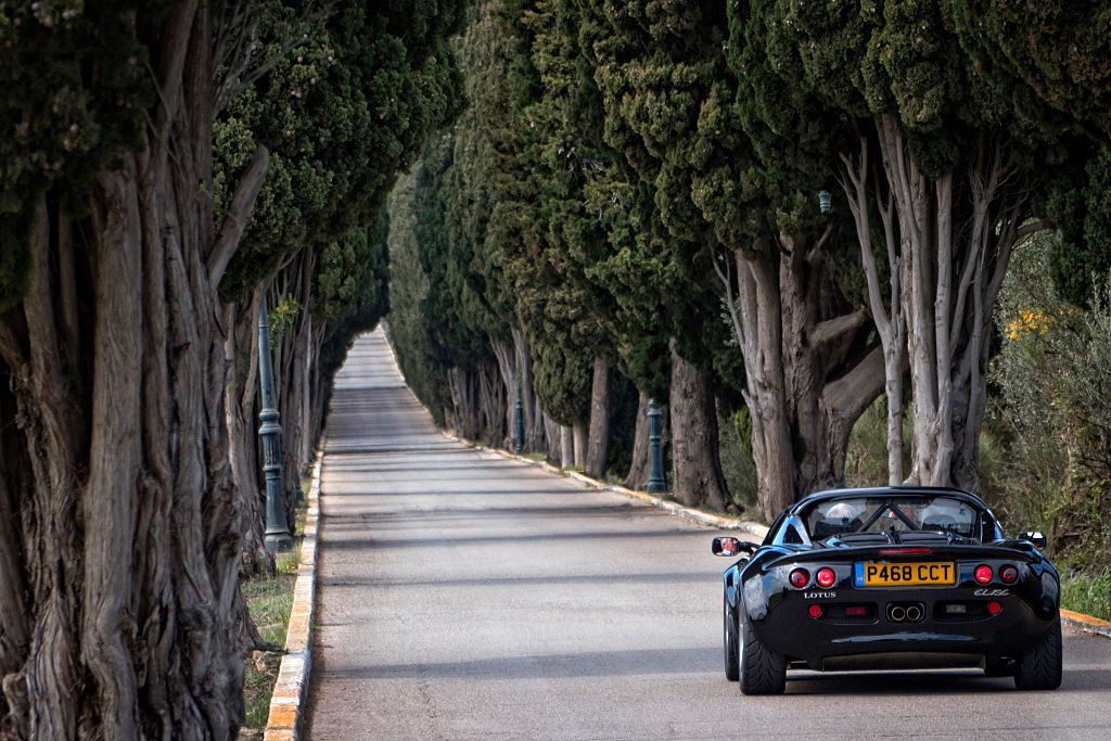 1 1997 Lotus Elise Sport 190 driving on a beautiful country road