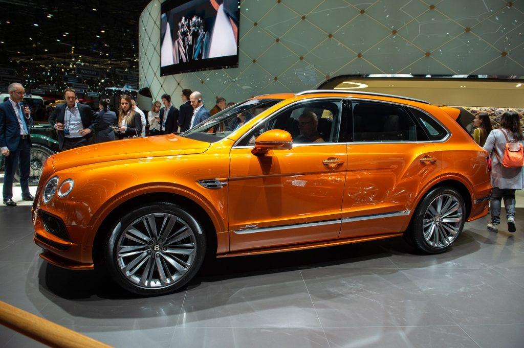 An orange Bentley Bentayga shines under the lights at a car show