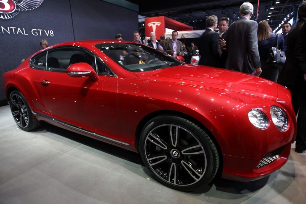 A red Bentley Continental GT sits on stage at a car show