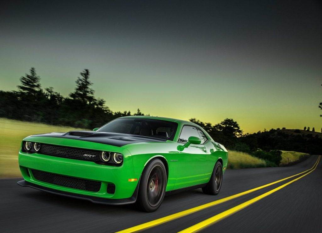 a bright green Dodge Challenger muscle car driving down a scene road at dusk