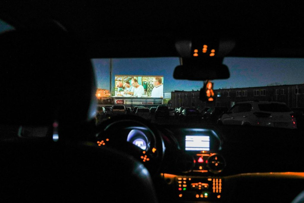 A view of the drive-in screen from inside a car at night