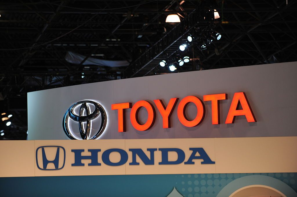 Toyota and Honda logos on display at an auto show are iconic images of a Japanese car company