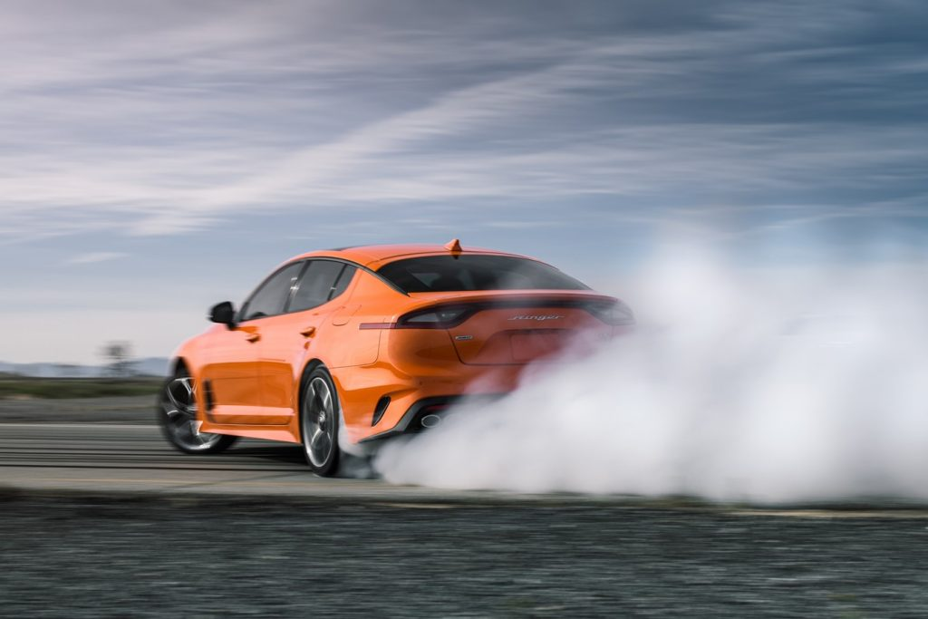 An orange Kia Stinger GTS performs a burnout