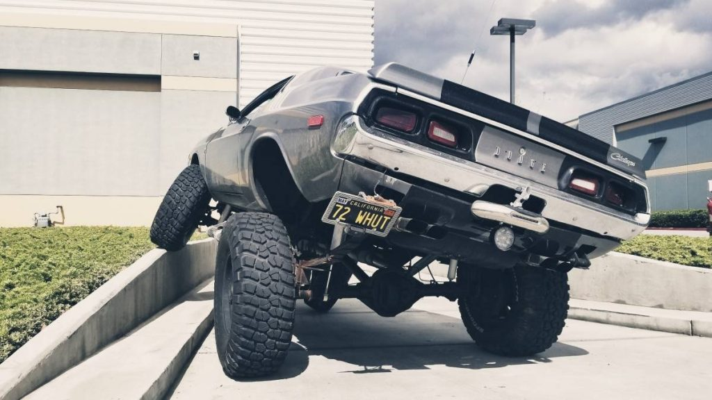 Lifted 1973 Dodge Challenger 4x4 rear view, as its front driver's wheel articulates over a concrete berm