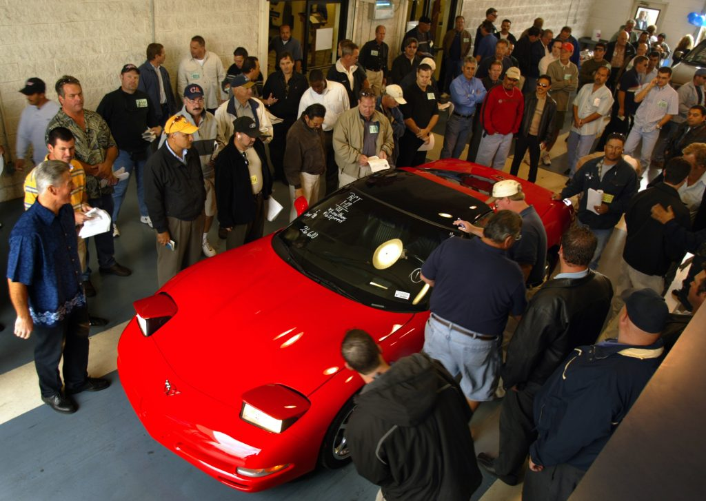 A red Corvette surrounded by dealers at a Manheim auction in California