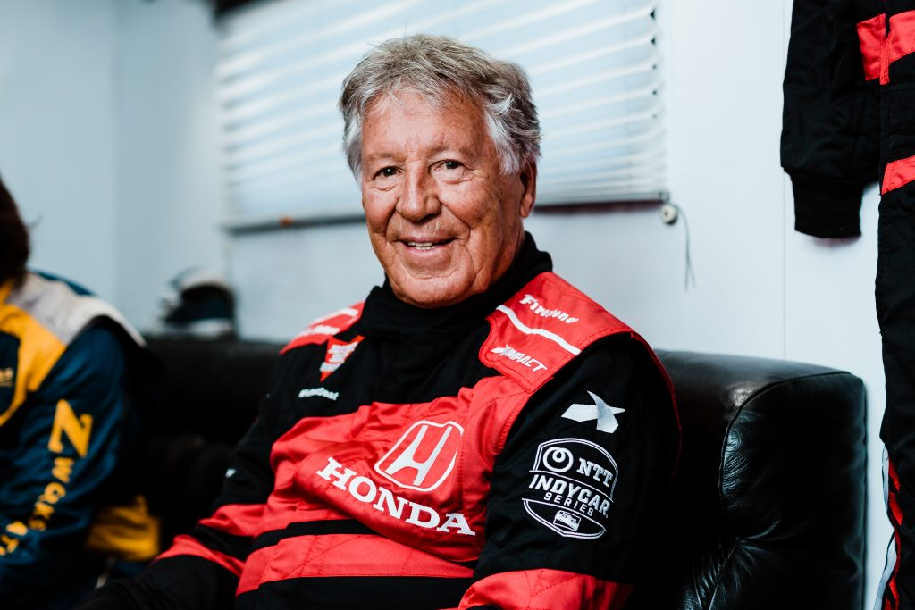 Mario Andretti on a seat in his race suit