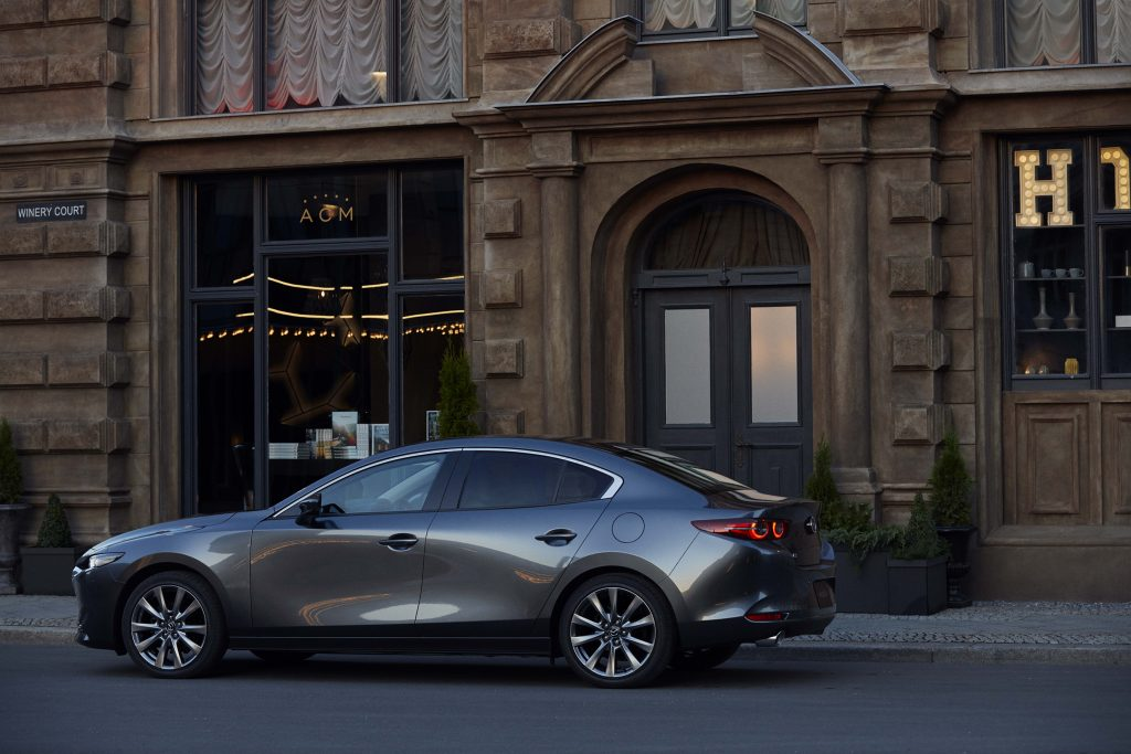 a gray Mazda 3 parked in the city