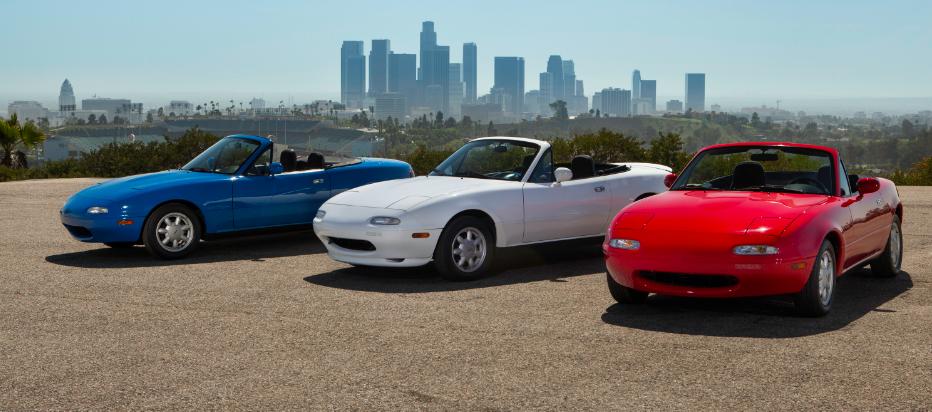 Three Mazda Miatas lines up outside.