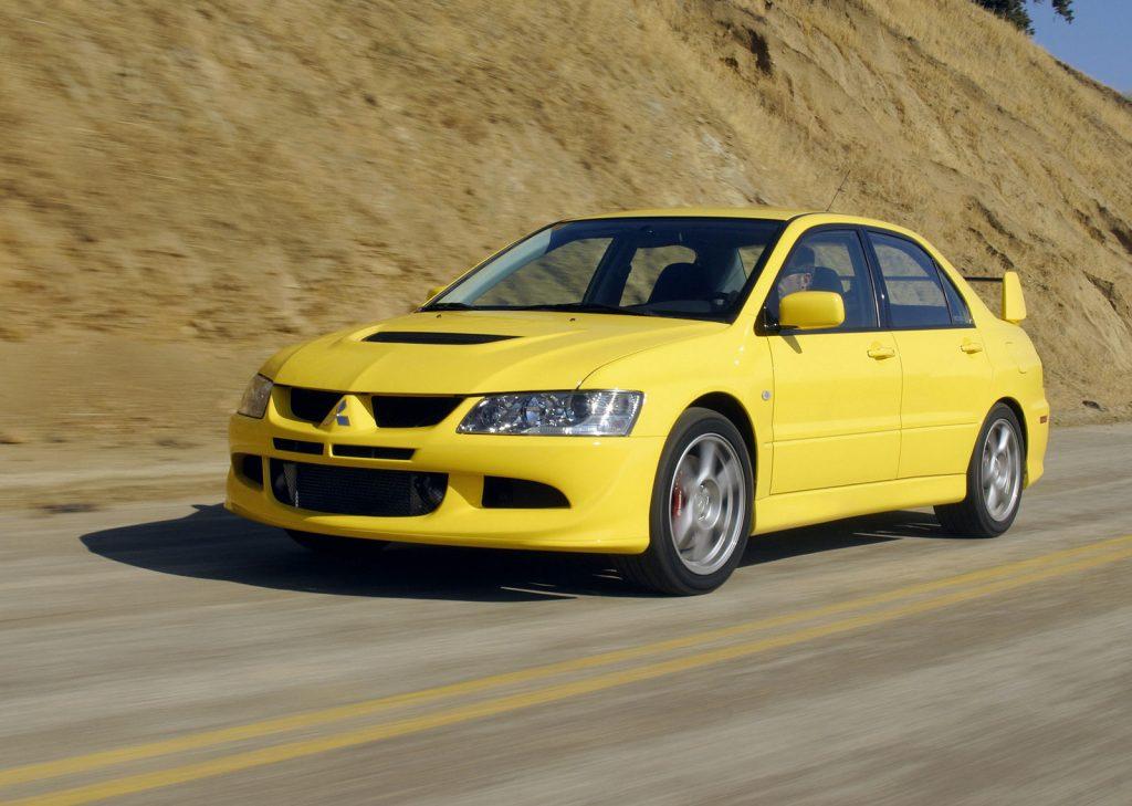 yellow Mitsubishi Lancer driving down highway