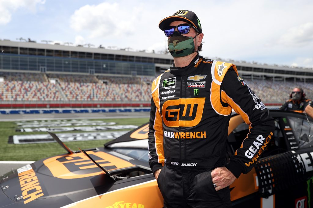 Driver Kurt Busch stands by his NASCAR racecar while wearing a facemask