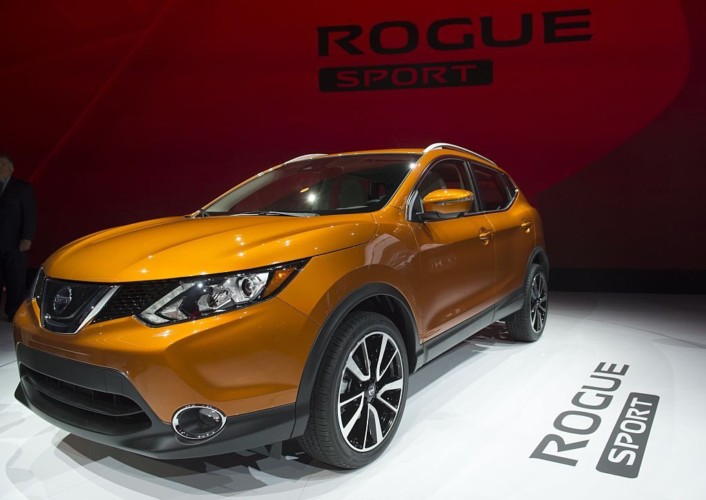 An orange Nissan Rogue Sport on display at an auto show