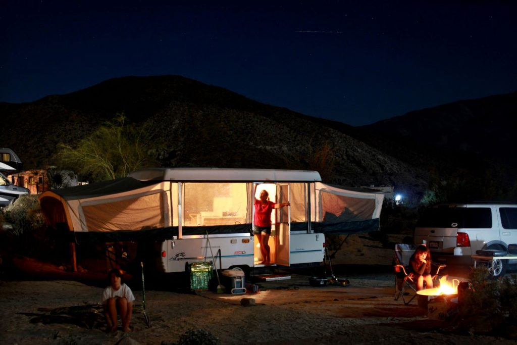 Pop-up camper set up in a campsite complete with a campfire