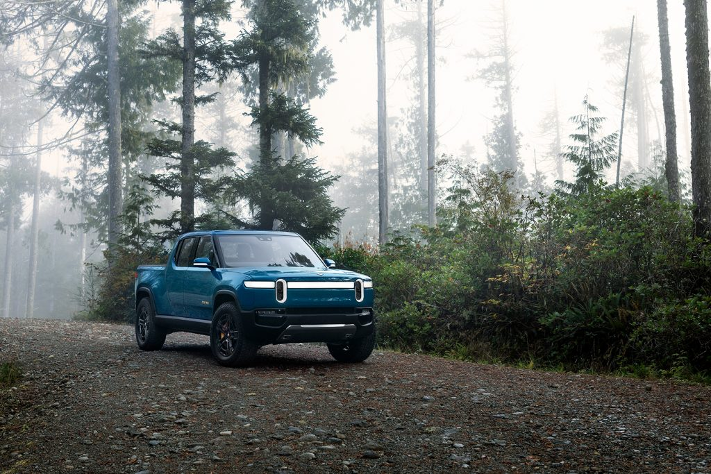 A blue Rivian R1T pickup on a forest road