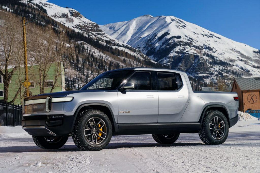 A silver Rivian R1T pickup sits at the base of snow-capped mountains