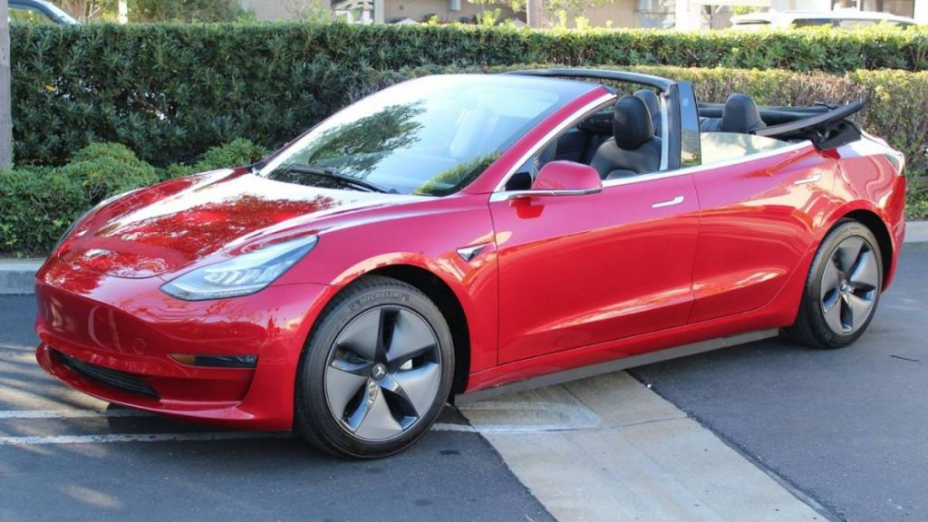 A red Tesla Model 3 has its soft top down
