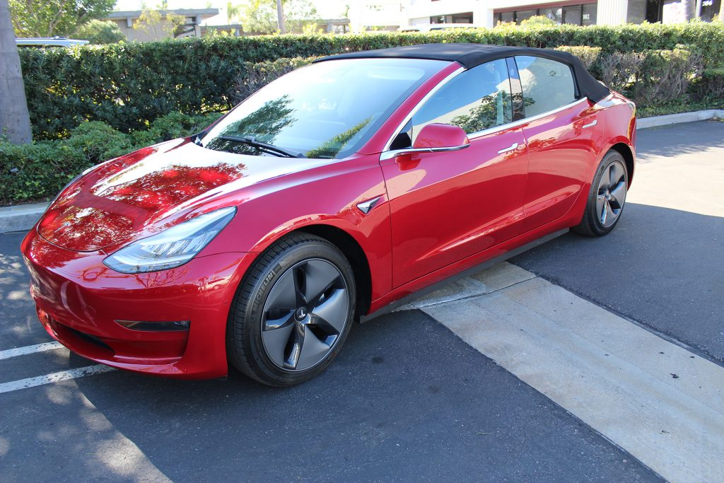 A red Tesla Model 3 convertible with its soft top up