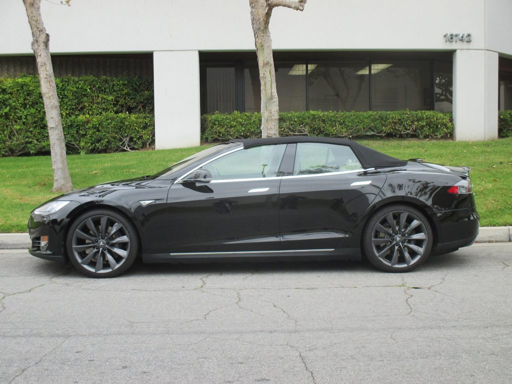 A black Tesla Model S with its convertible top up