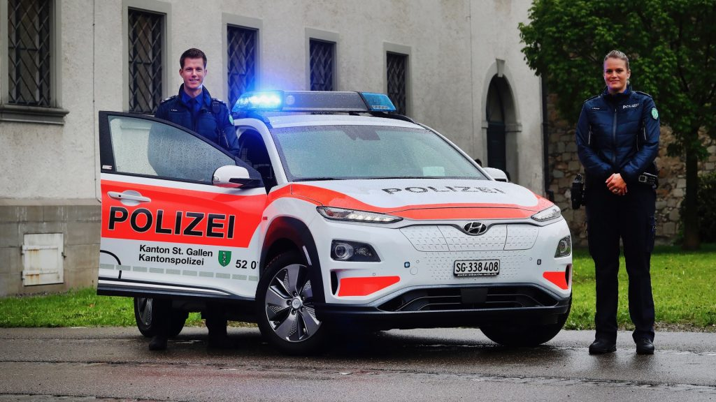 Police officers stand by a Hyundai Kona Electric that has police livery