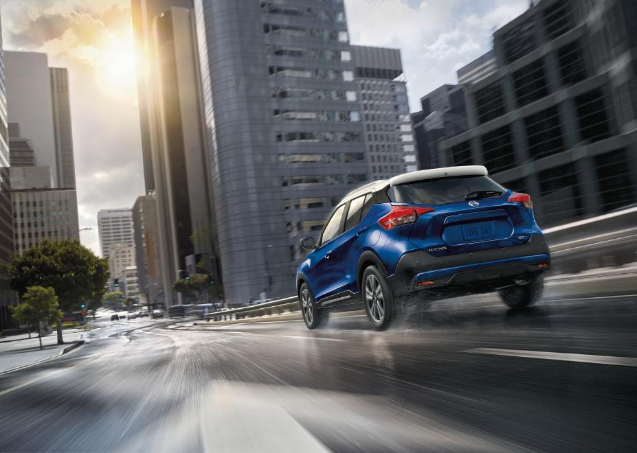a blue Nissan Kicks navigating city streets
