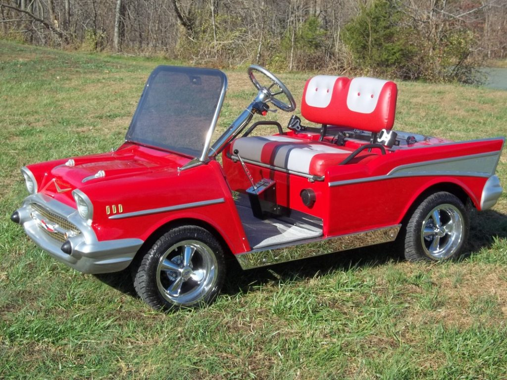A red 1957 Chevy bodied golf cart sits in a yard