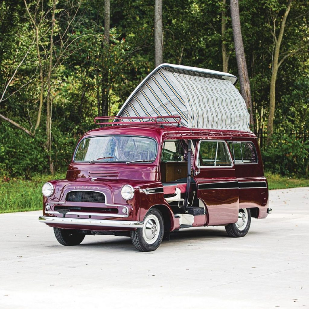 Maroon 1961 Bedford CA Dormobile camper van with its pop-up roof open in front of a forest