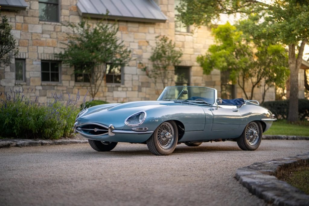 Light-blue 1966 Series 1 Jaguar E-Type convertible in front of a country estate