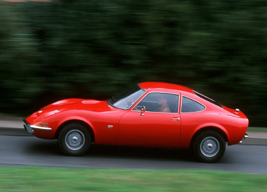 Red 1968 Opel GT, driving down the road, side view