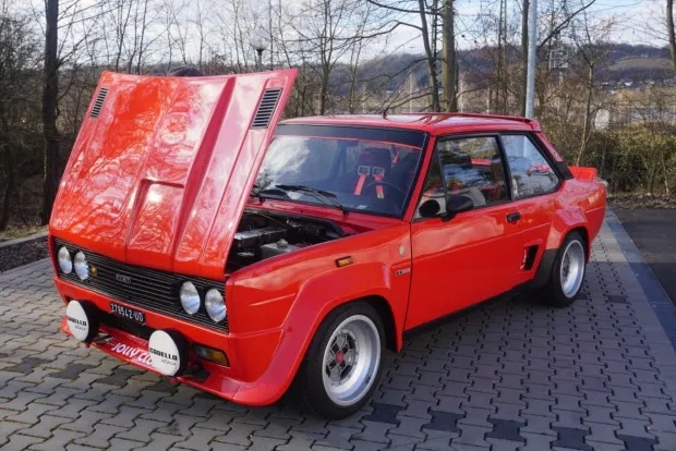Red 1976 Fiat 131 Abarth Rally with its hood opened