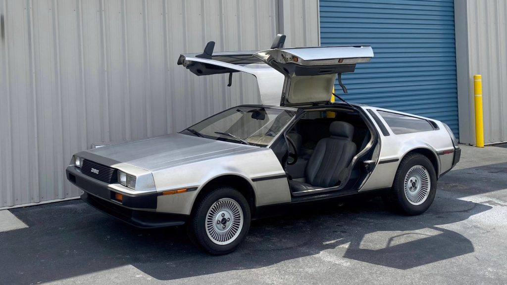 Stainless-steel 1981 DeLorean DMC-12 parked with the doors up
