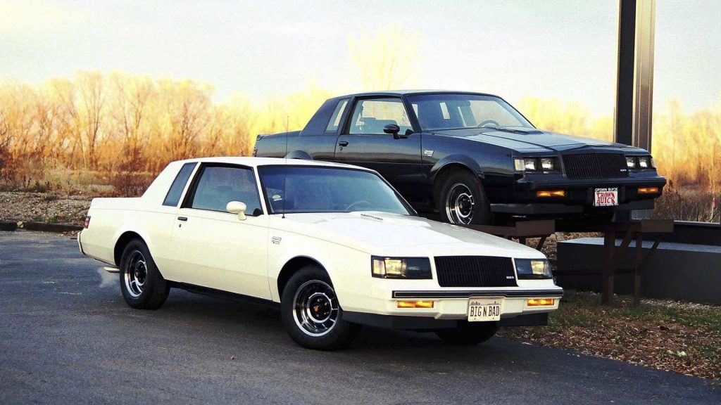 A white Buick Regal T-Type and a black Buick Grand National sit beside each other.
