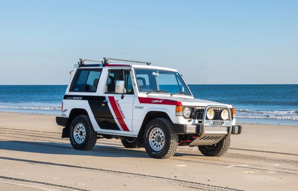 The white-with-black-and-red-stripes 1988 Mitsubishi Pajero Paris-Dakar Special classic SUV driving down the beach