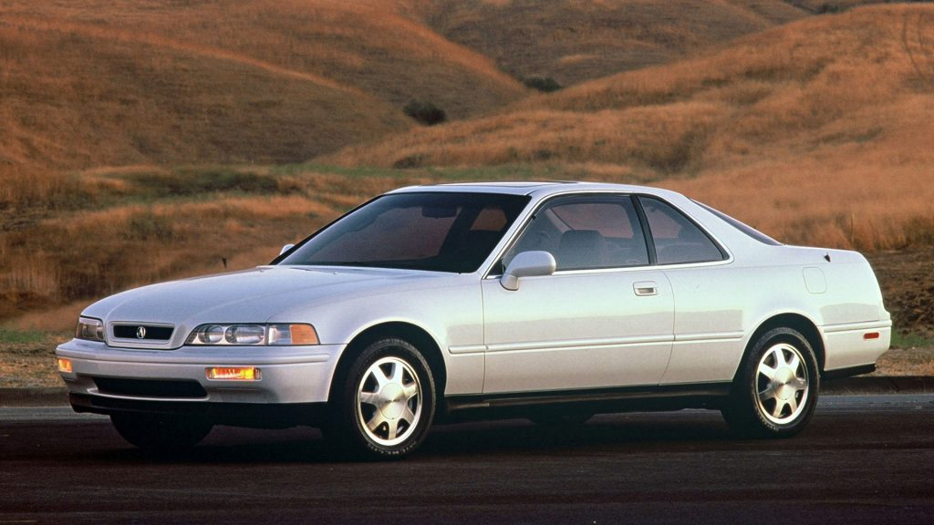 A white Acura Legend coupe sits before rolling hills.