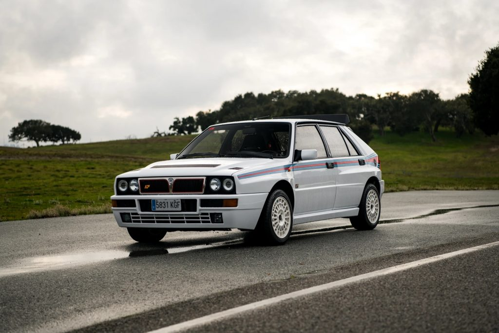 White with red-and-blue stripes 1992 Lancia Delta Integrale Evoluzione I Martini 5 Edition hot hatch on a wet road in front of a grassy hill
