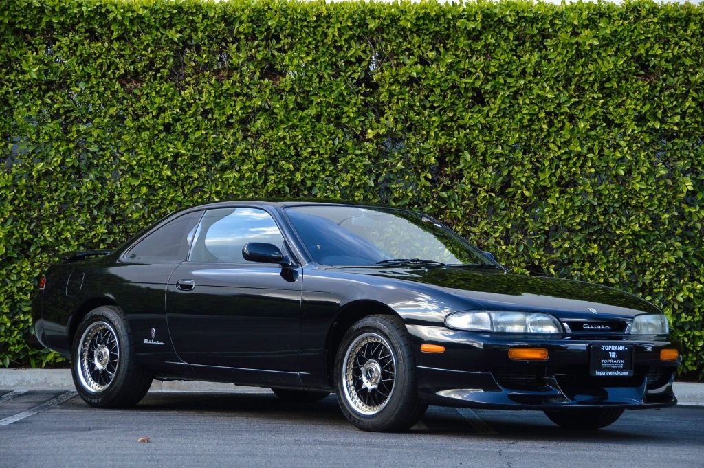 Black 1994 Nissan Silvia coupe in front of a hedge