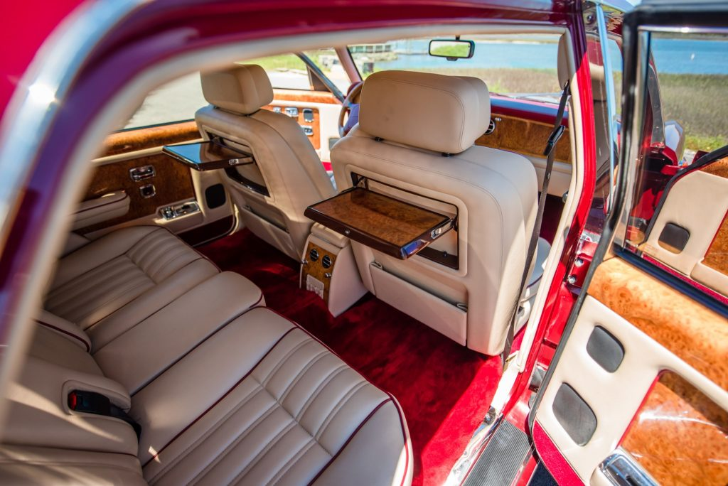 Tan leather and wood-trimmed interior of a red 1996 Rolls-Royce Silver Spur