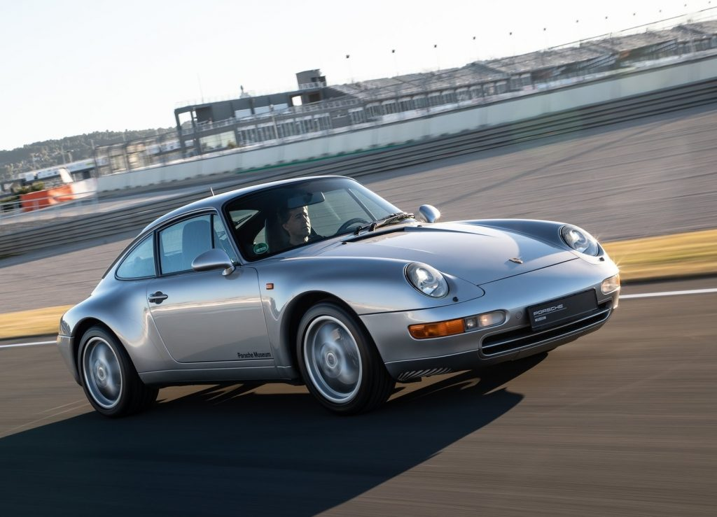 Silver 1997 993 Porsche 911 Carrera driving around a racetrack