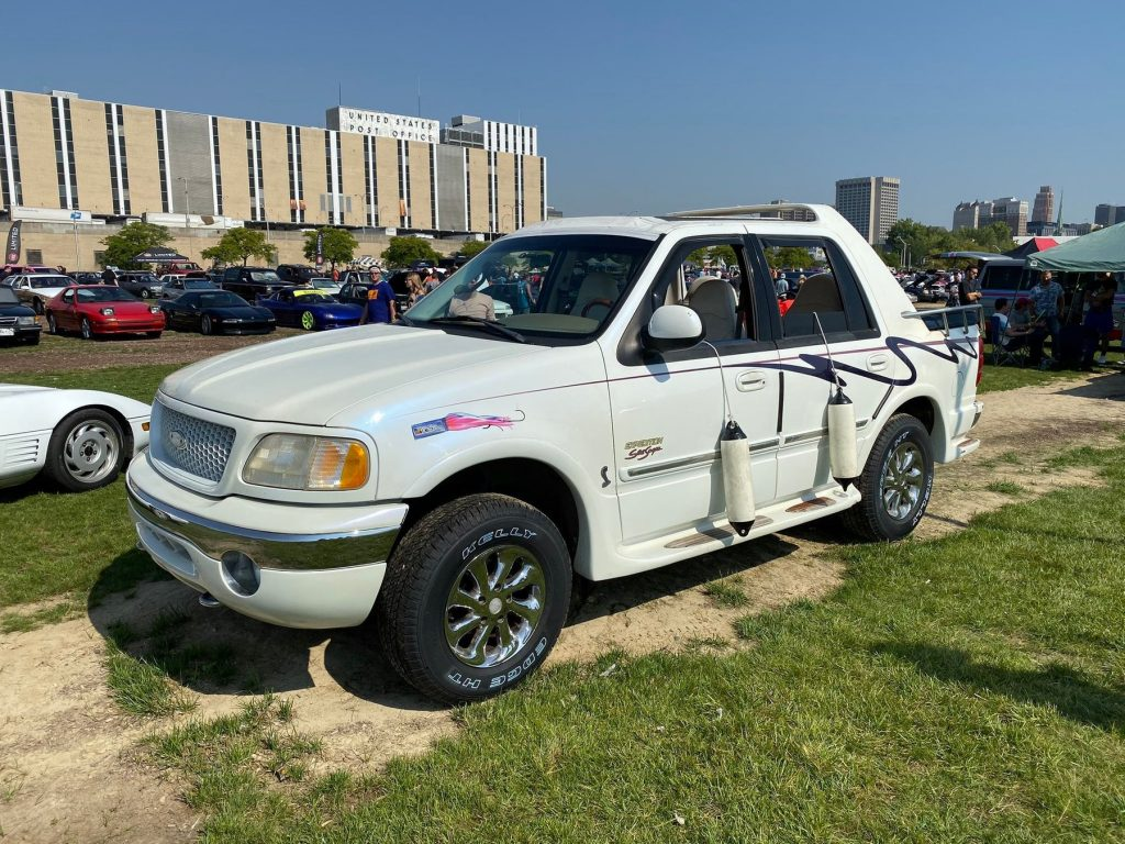 A white nautical themed Ford Expedition parked at a car show.