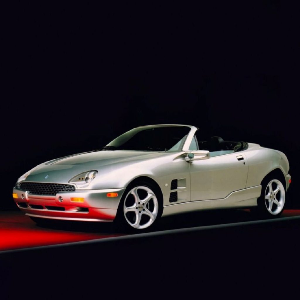 Silver 1999 Qvale Mangusta with the roof down against a black background