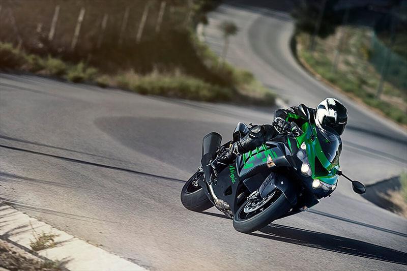 a bright green Kawasaki ninja zx-14r speeding through a winding turn