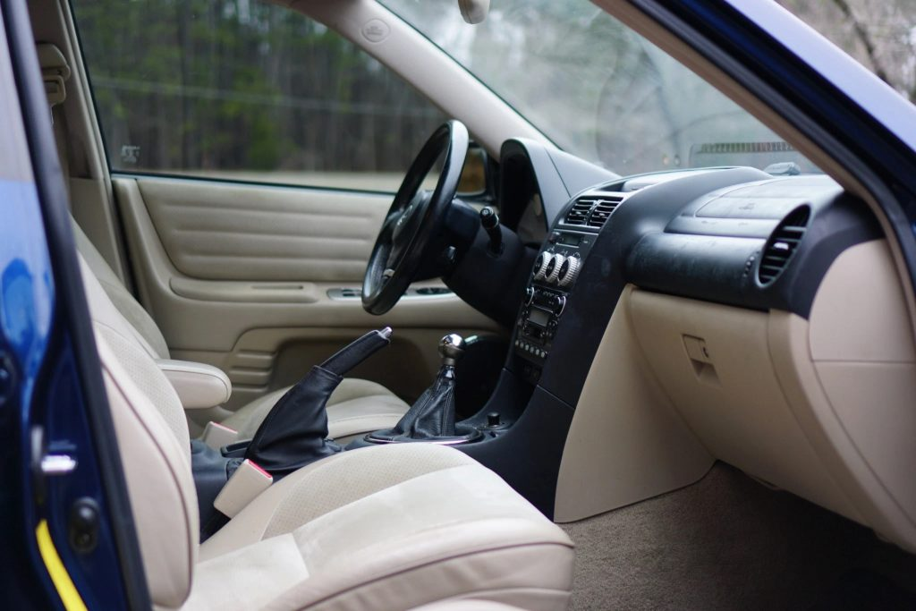The tan leather front seats and black dashboard of a 2002 Lexus IS300