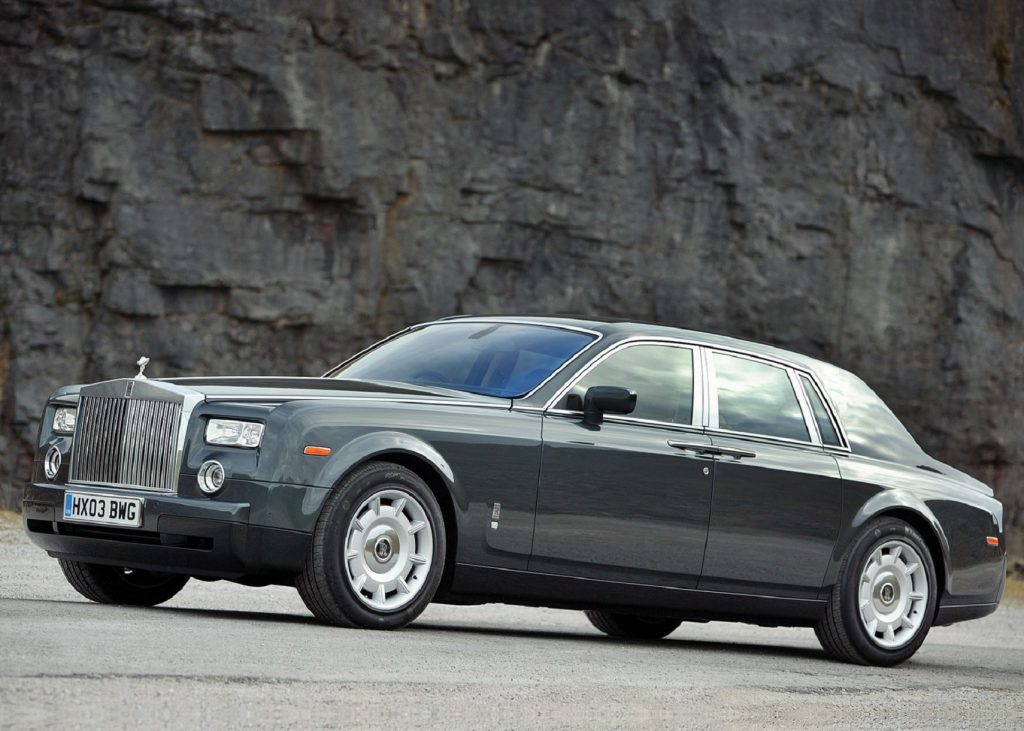 Gray 2003 Rolls-Royce Phantom VII side view, in front of a rocky cliff