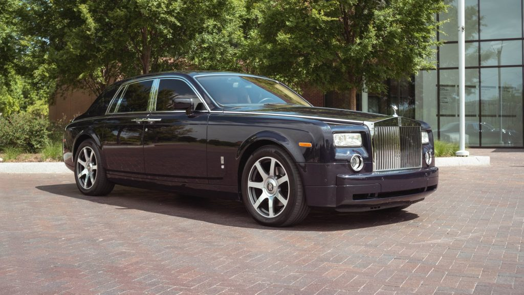 A blue Rolls-Royce Phantom sits in front of office building