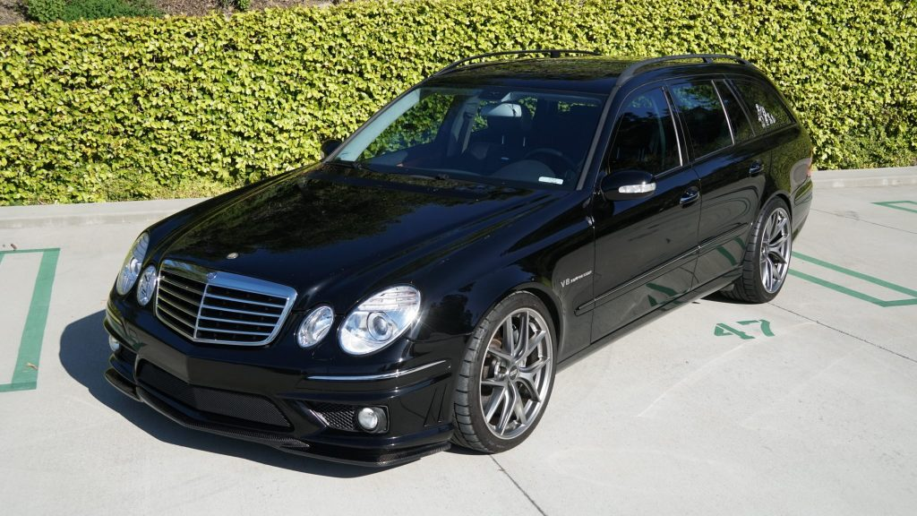 Black 2006 Mercedes E55 AMG Wagon in front of a green hedge