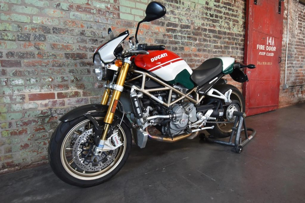 2008 Ducati Monster S4R S Tricolore motorcycle, with a tank painted in the Italian flag's colors, against a brick wall